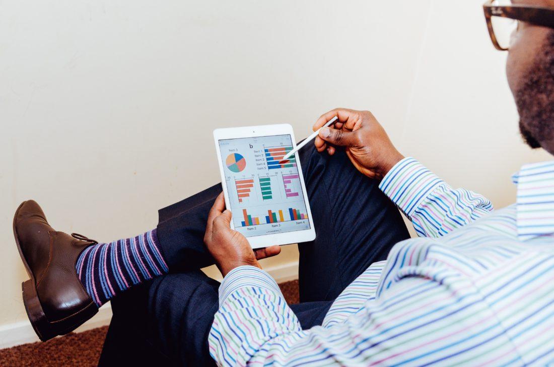 Ein Mann sitzt mit seinem Tablet und übereinenadergeschlagenen Beinen auf einer Bank. Auf dem Bildschrim sind farbige Diagramme zu sehen.