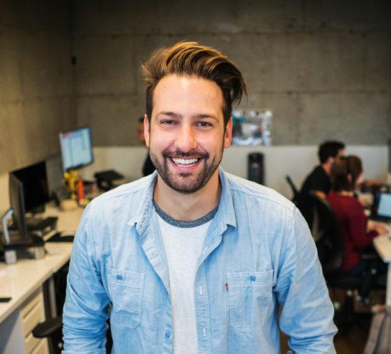 Glückliche Mitarbeiter wie dieser junge Mann prägen den Unternehmenserfolg entscheidend. Deshalb sollte in deren Gesundheit und Wohlbefinden mit digitalen Lösungen investiert werden.
