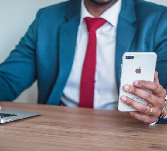 Mann, der mit Smartphone am Laptop sitzt und Sinnbild für Corporate Influencer ist