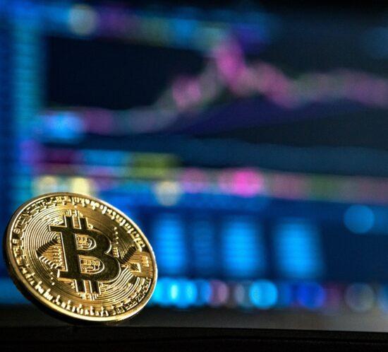 ein Bitcoin steht vor einem Bildschirm, er steht sinnbildlich für die Blockchain und dem Zusammenhang mit Bitcoins
