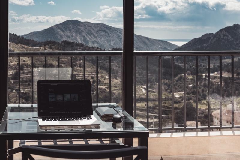 Ein Arbeitsplatz mit Sicht auf eine bergige Landschaft steht repräsentativ für den arbeitsplatz der Zukunft