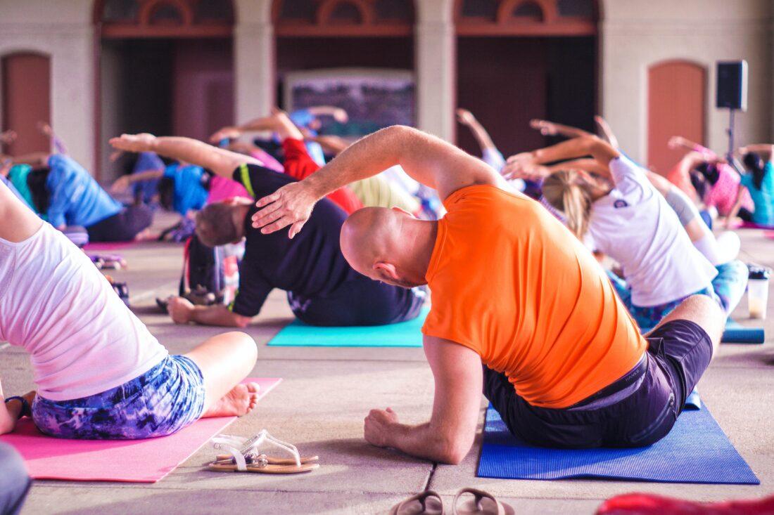 eine Gruppe macht Yoga. Sie stehen für die Fringe Benefits in einem Unternehmen, von denen Arbeitnehmende profitieren