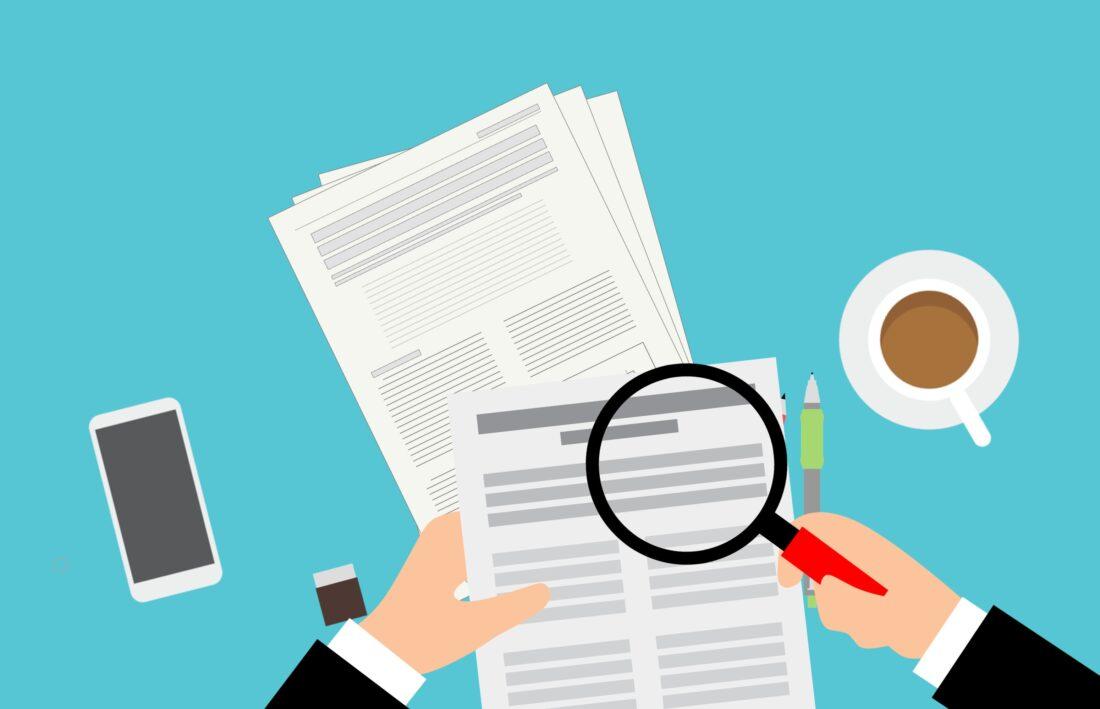 eine Illustration mit Papieren und einer Lupe stehen für Assessments im Recruiting
