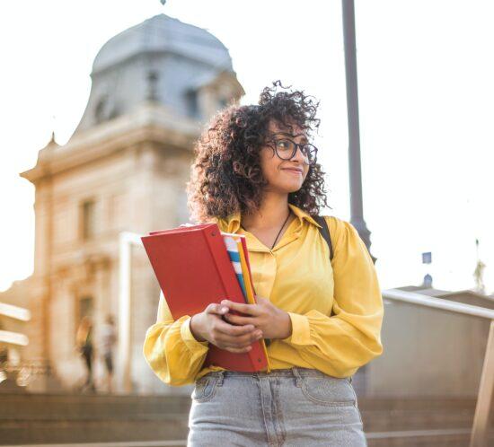 eine junge Frau steht mit Mappe vor einem Gebäude und lächelt