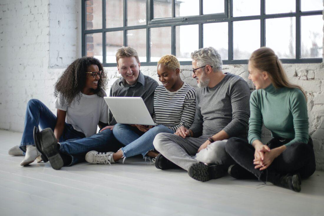 Eine Gruppe Menschen unterschiedlichen Alters sitzen und schauen auf einen Computer