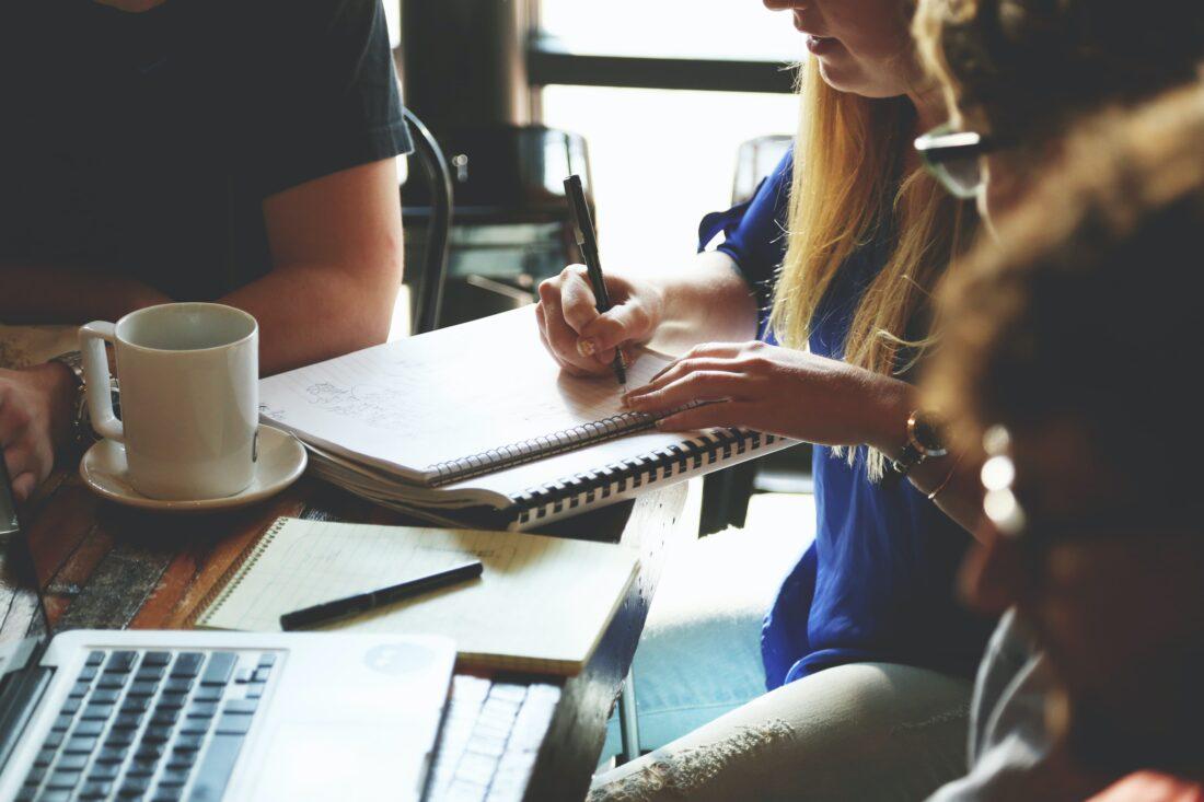 Eine Gruppe junger Menschen sitzt an einem Tisch und schaut auf einen Notizblock