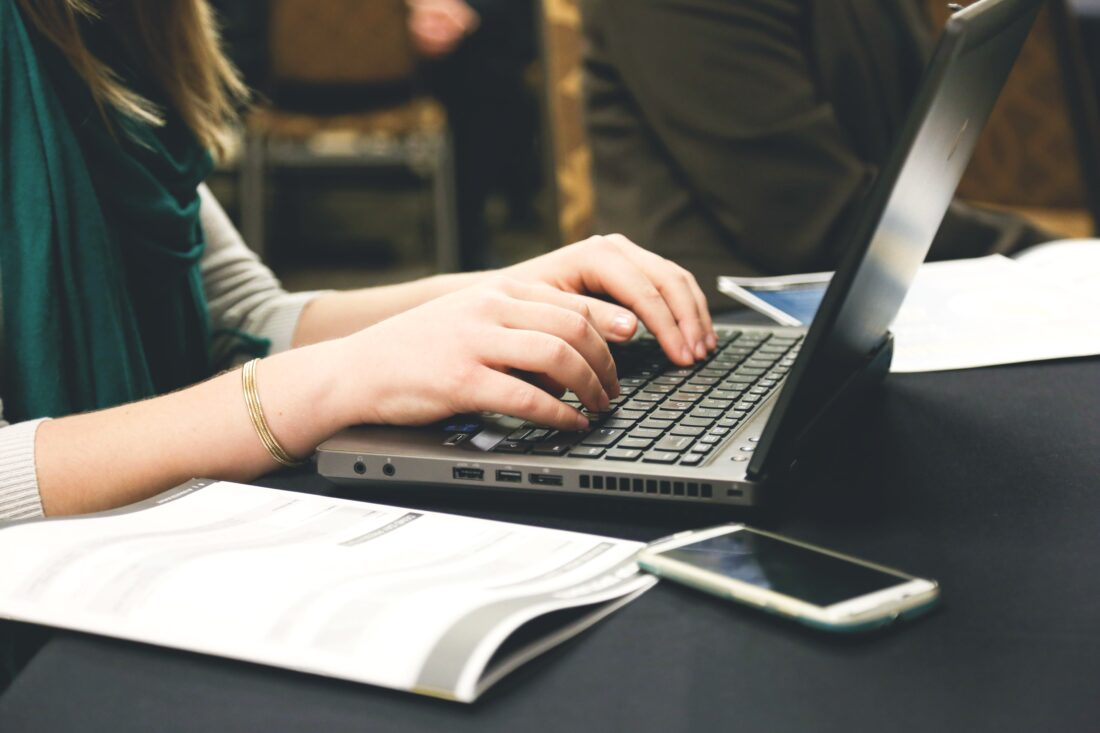 Ein Ausschnitt von einer Person, die auf einem Laptop schreibt