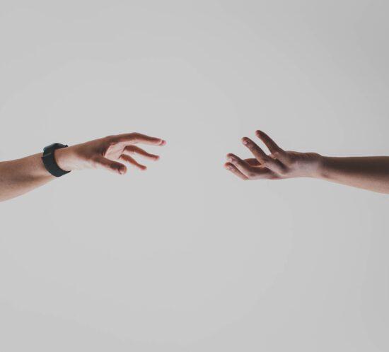 Zwei ausgestreckte Arme greifen nacheinander