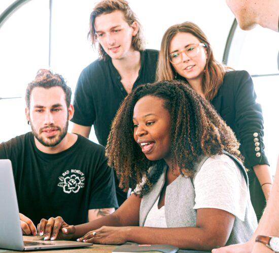Eine Gruppe junger Leute schaut gespannt in einen Laptop rein