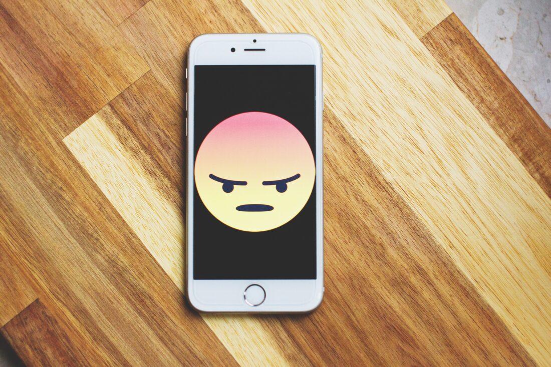 Ein Smartphone mit einem wütenden Smiley ist abgebildet