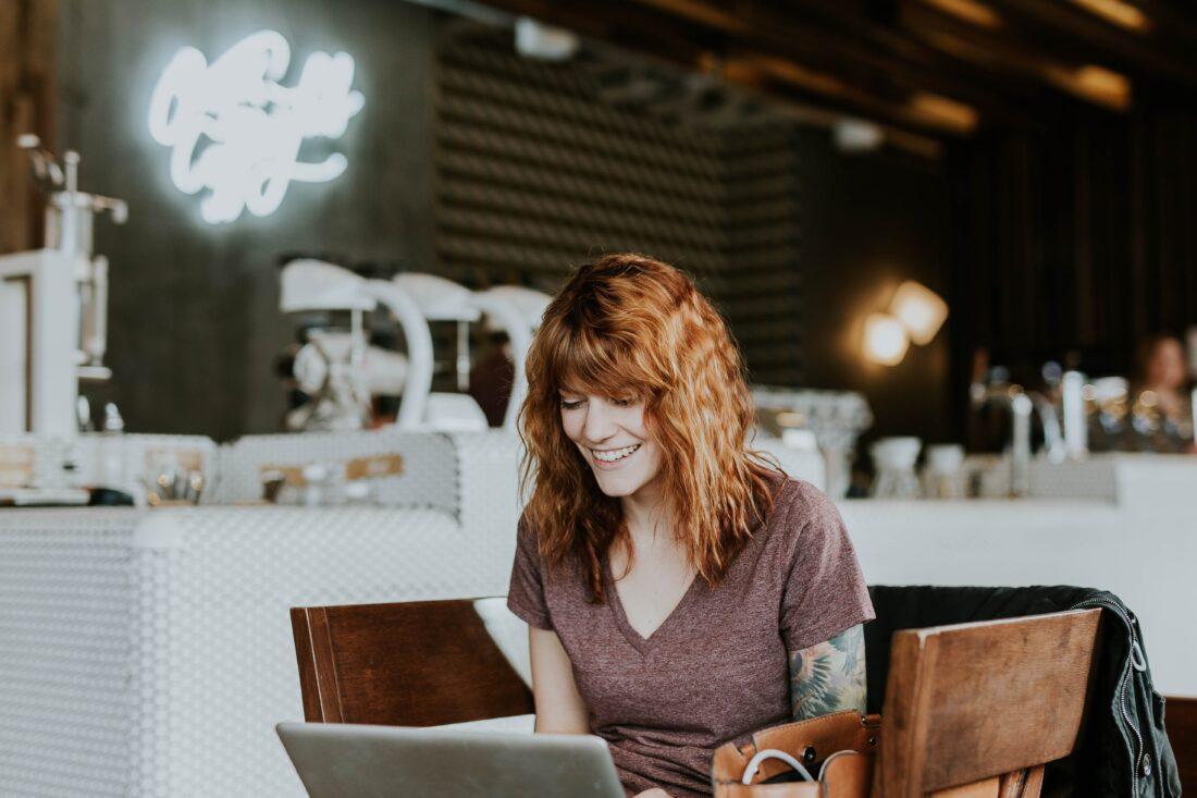 Eine Frau lacht in ihren Laptop hinein. Sie sitzt an einem Tisch