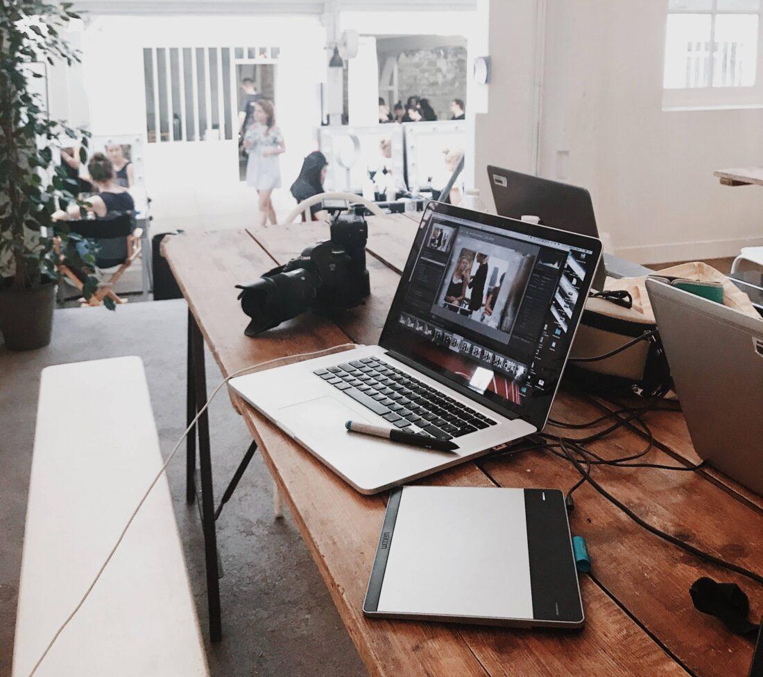 Ein Holztisch mit Pc, Tablett und Kamera in einem Büro